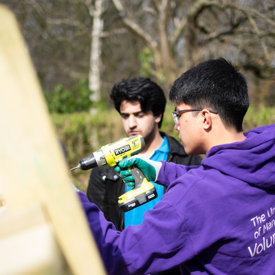 Students volunteering in Whitworth Park building a wooden garden pagoda