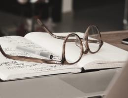 Glasses on an open notebook with notes